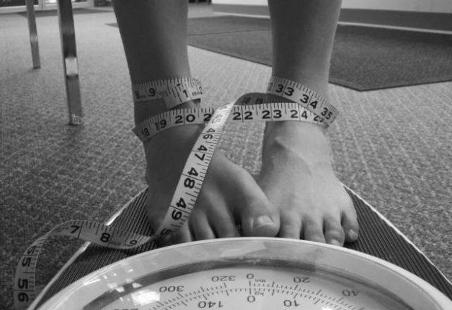 donna magra mentre si pesa sulla bilancia